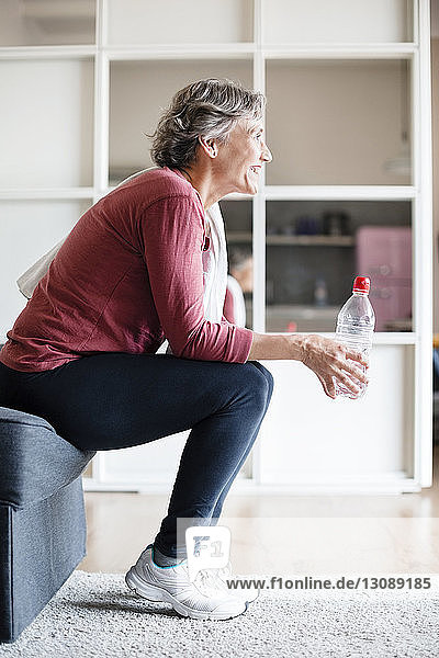Side view of sporty mature woman holding water bottle while sitting on sofa at home