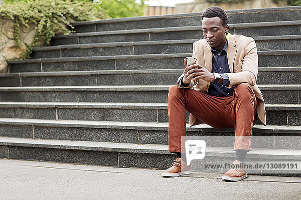 Full length of businessman using smart phone while sitting on steps