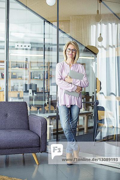 Porträt einer selbstbewussten Geschäftsfrau mit Laptop-Computer am Fenster im Büro