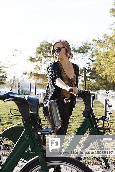 Glückliche Frau mit Fahrrad im Park