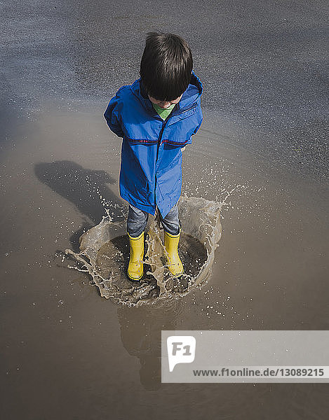 High angle view of playful boy wearing rubber boots while jumping in puddle