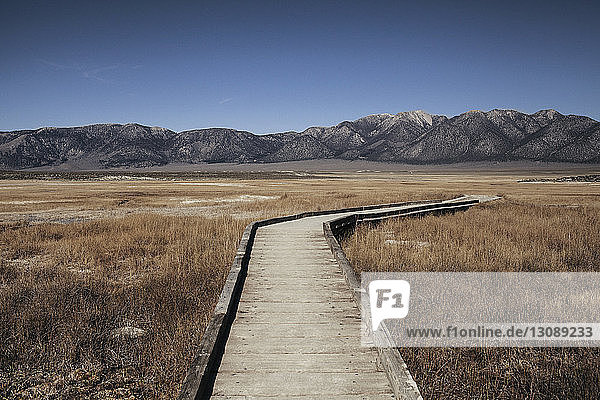 Wooden boardwalk on grassy field against mountains at Mammoth Lake Hot Springs
