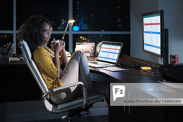 Side view of thoughtful businesswoman holding coffee cup while sitting on chair in office at night