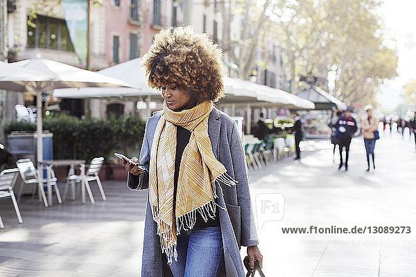 Frau mit lockigem Haar benutzt Mobiltelefon beim Gehen auf der Straße in der Stadt