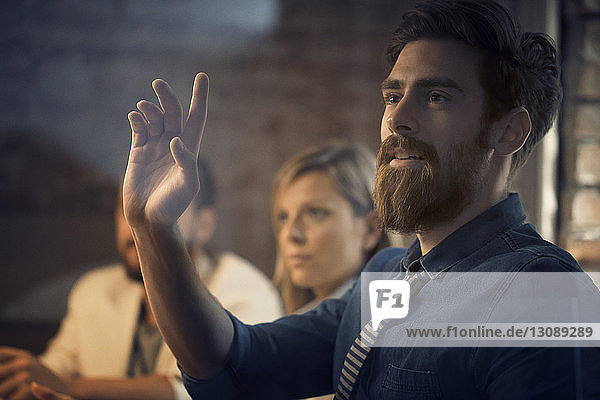 Businessman raising hand during meeting