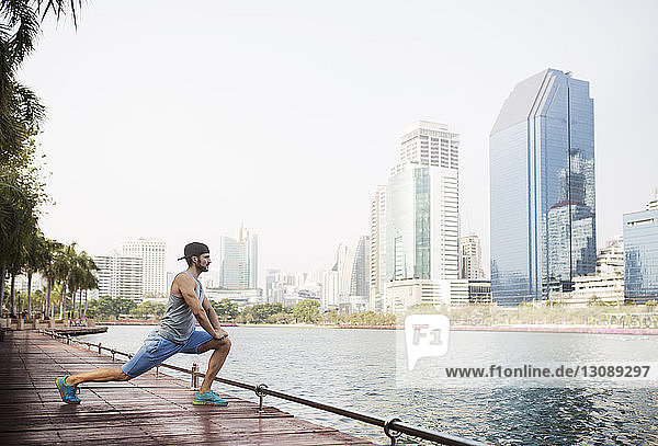 Side view of man stretching on wooden walkway by river against sky