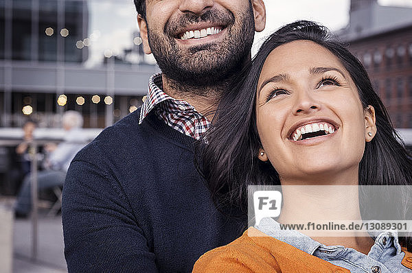Young woman laughing with her boyfriend in city