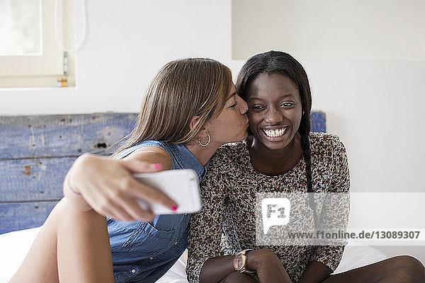 Frau nimmt Selbstliebe während sie eine Freundin im Schlafzimmer küsst