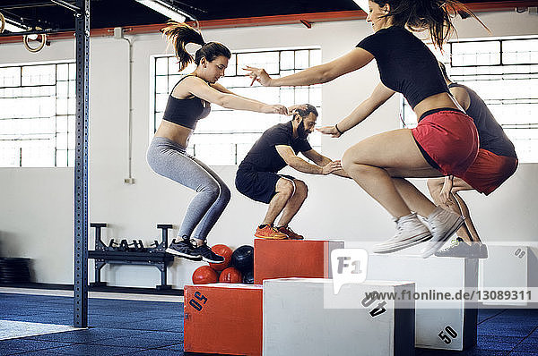 Athletes box jumping in gym