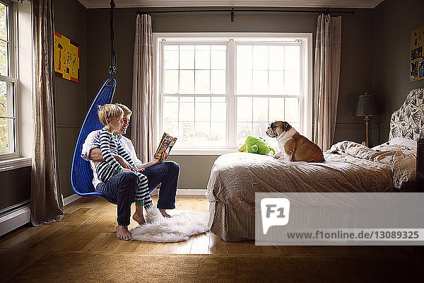 Father reading book to son while dog sitting on bed by window