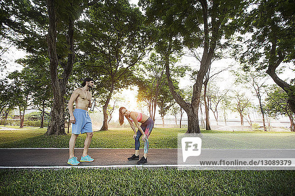 Exhausted couple relaxing after exercising at park