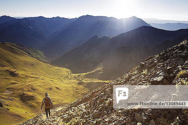 Rückansicht einer auf Bergen gehenden Frau vor klarem Himmel