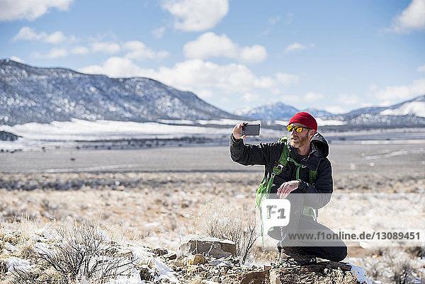 Wanderer fotografiert mit Smartphone in voller Länge im Winter in der Wüste gegen die Berge