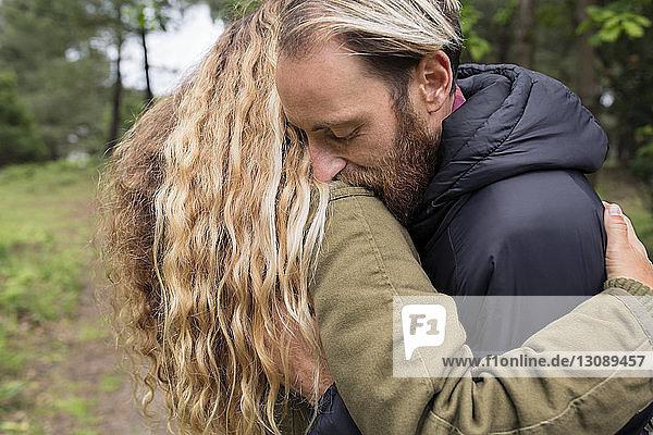 Seitenansicht eines sich im Wald umarmenden Liebespaares