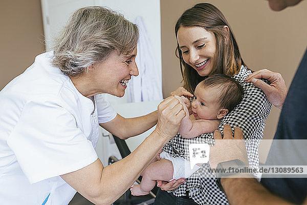 Lächelnde Mutter schaut den Arzt an  der mit dem kleinen Jungen im Untersuchungsraum spielt