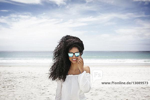 Porträt einer glücklichen Frau  die am Strand gegen den Himmel steht