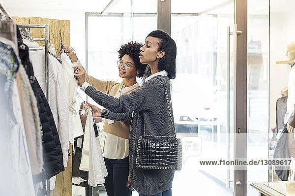 Freunde wählen an sonnigen Tagen Hemden im Kleiderständer am Eingang des Geschäfts
