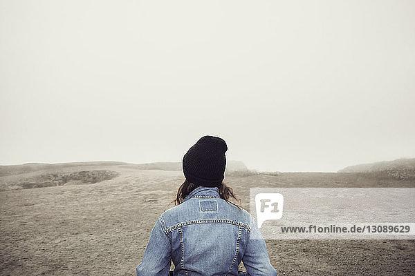 Rückansicht einer auf einer Klippe stehenden Frau vor klarem Himmel