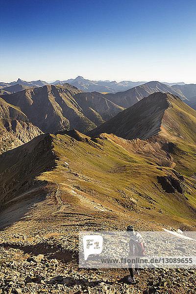 Rückansicht einer Rucksacktouristin  die bei klarem Himmel auf Bergen wandert