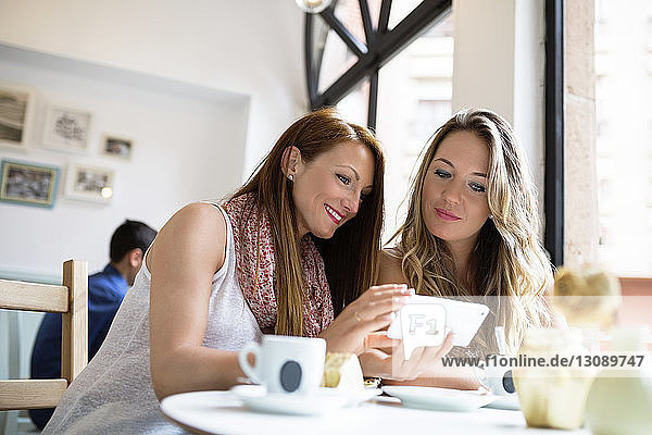 Female friends using mobile phone at cafe table