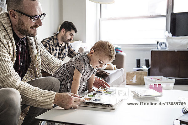 Father showing picture book to daughter with partner sitting in background
