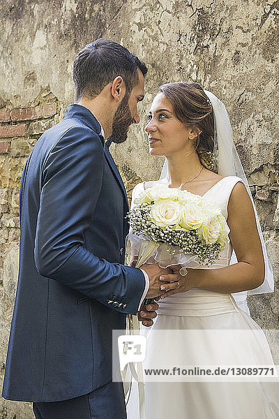 Romantic newlywed couple looking at each other while standing by old wall