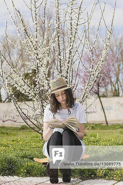 Junge Frau liest in voller Länge ein Buch  während sie im Park auf einem Skateboard sitzt