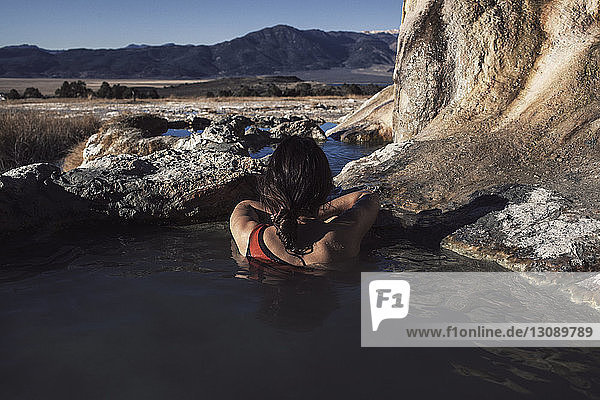 Rear view of woman relaxing in Bridgeport Hot Springs