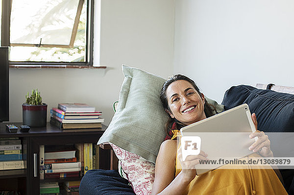 Porträt einer schwangeren Frau  die einen Tablet-Computer benutzt  während sie zu Hause auf dem Sofa liegt