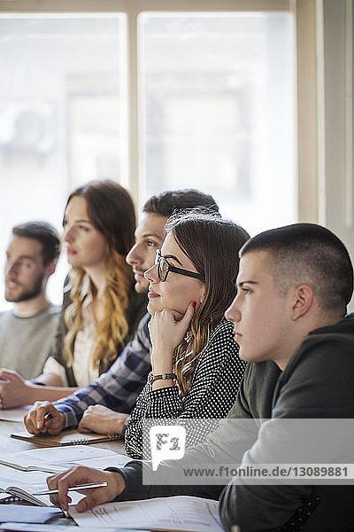 Schüler konzentrieren sich  während sie im Klassenzimmer sitzen