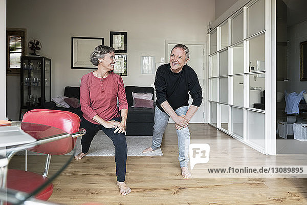 Happy senior couple doing stretching exercise at home