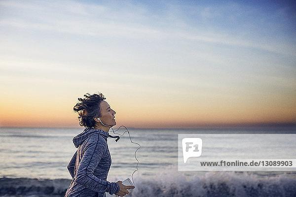 Woman jogging at beach against sky