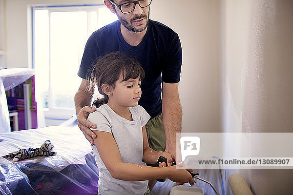 Father assisting daughter in painting wall at home