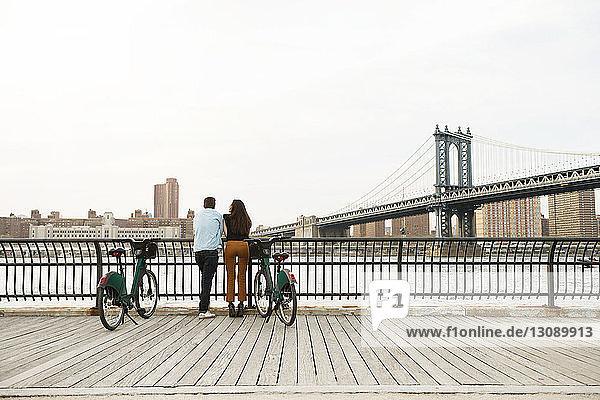 Paar steht mit Fahrrädern auf Fußweg an der Manhattan-Brücke gegen den Himmel