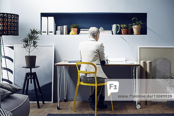Rear view of woman working at table in creative office