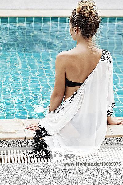 Rückansicht einer Frau  die sich am Pool entspannt