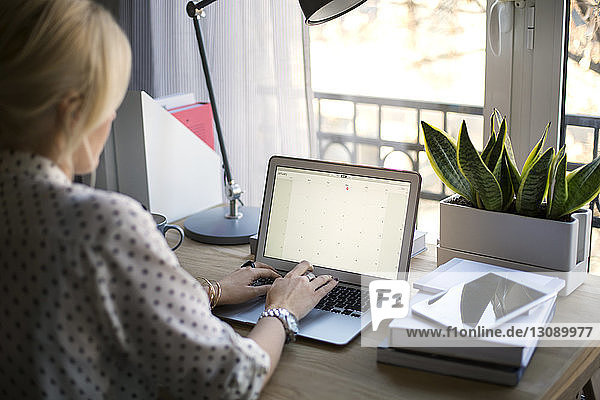 Rear view of woman using laptop at home office