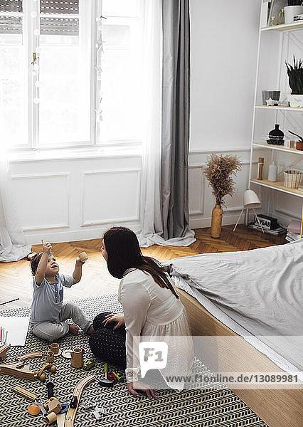 Schrägaufnahme eines kleinen Jungen  der eine Spielzeug-Teetasse hält  während er mit der Mutter auf dem Teppich im Schlafzimmer sitzt