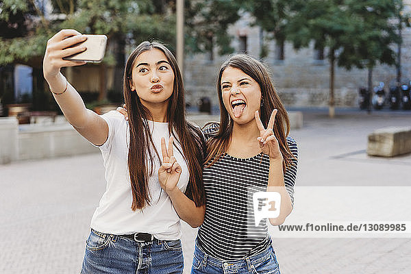 Friends taking selfie with mobile phone while standing on street