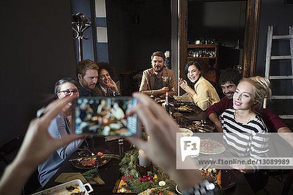 Ausschnitt einer Frau  die glückliche Freunde beim Essen fotografiert