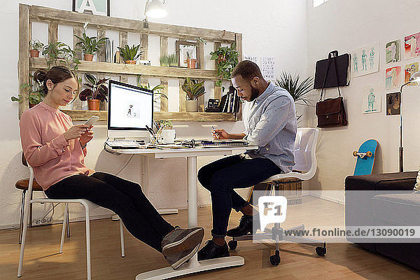 Männlicher Illustrator arbeitet  während eine Kollegin ein Smartphone im Kreativbüro benutzt