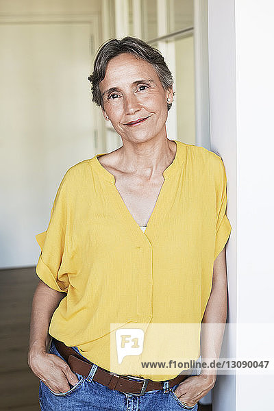 Portrait of confident mature woman standing at home