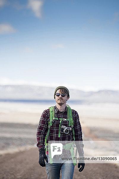Wanderer mit Kamera erkundet Wüste gegen Himmel