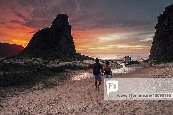 Rückansicht eines Paares  das bei Sonnenuntergang auf Sand gegen den Himmel läuft