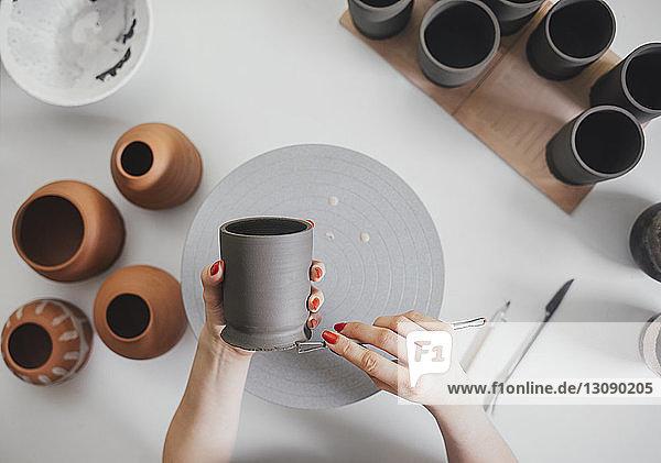 Geschliffene Hände einer Töpferin  die bei Tisch in der Werkstatt Keramik herstellt Geschliffene Hände einer Töpferin, die bei Tisch in der Werkstatt Keramik herstellt
