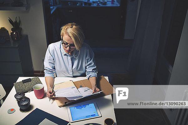 Schrägansicht einer Geschäftsfrau  die Dokumente liest  während sie im Heimbüro am Schreibtisch sitzt