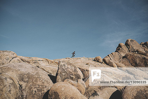 Mid distance view of boy running on rock formations against sky at desert