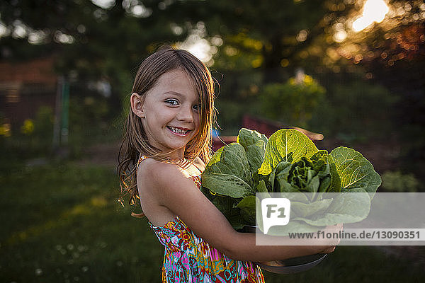 Happy girl carrying lettuce in bowl at backyard