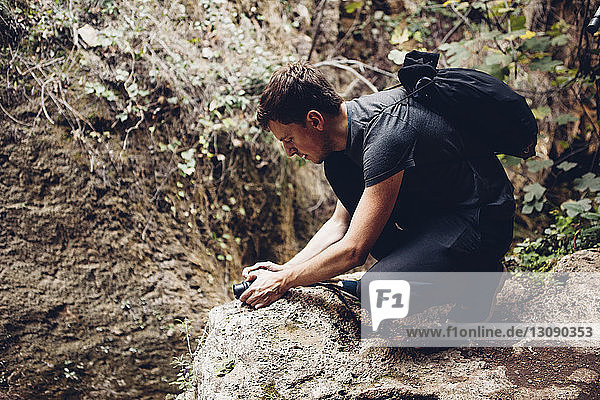 Male hiker with backpack photographing through camera while crouching on rock formation