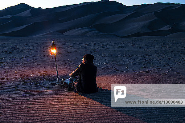 Rear view of man sitting on sand with illuminated lantern
